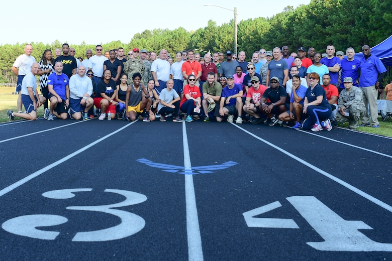 Participants in this year's Sept. 11 Memorial Walk pose for a photo at the base track Sept. 11, 2019.