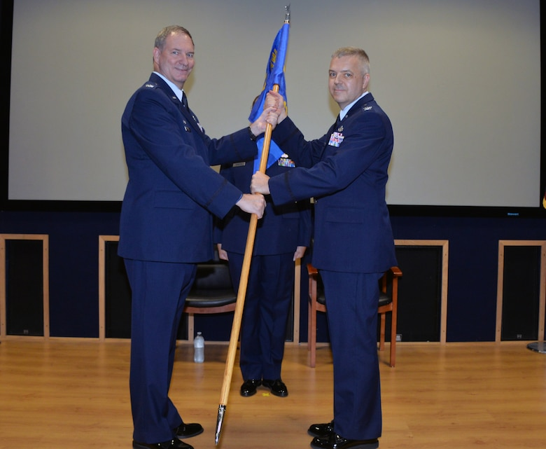 Col. Terry W. McClain, 433rd Airlift Wing commander, presents the 433rd Mission Support Group guidon to Col. Wayne M. Williams as he assumes command at Joint Base San Antonio-Lackland, Texas Sept. 7, 2019.