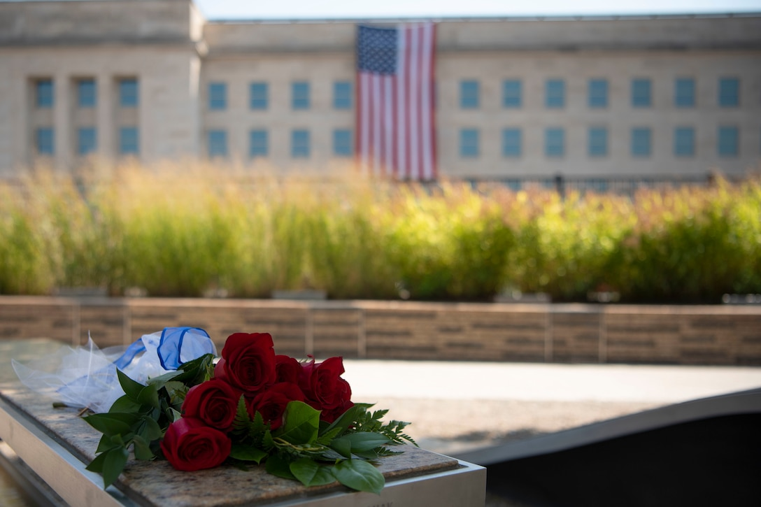 A bouquet of red roses lies on a bench outside the Pentagon.