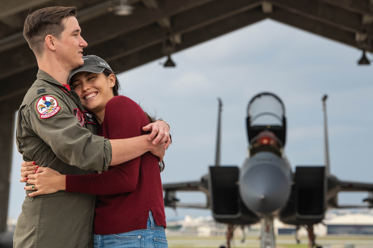 Air Force pilot in green flight suit and his wife, wearing a red shirt and jeans, share a hug in front of an F-15C fighter jet.