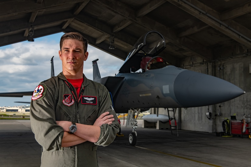 Air Force pilot in green flight suit stands with arms crossed in front of an F-15C fighter jet.