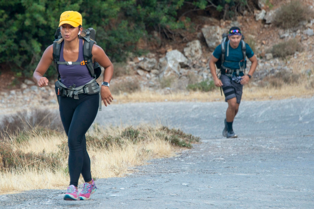 Hikers with backpacks walk on a trail.