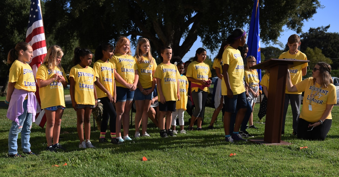 Children read a poem for those who died on 9/11 before the Remembrance Day Freedom Walk, Sept. 11, 2019, at Travis Air Force Base, California. The walk commemorated those who lost their lives on 9/11. (U.S. Air Force photo by Airman 1st Class Cameron Otte)