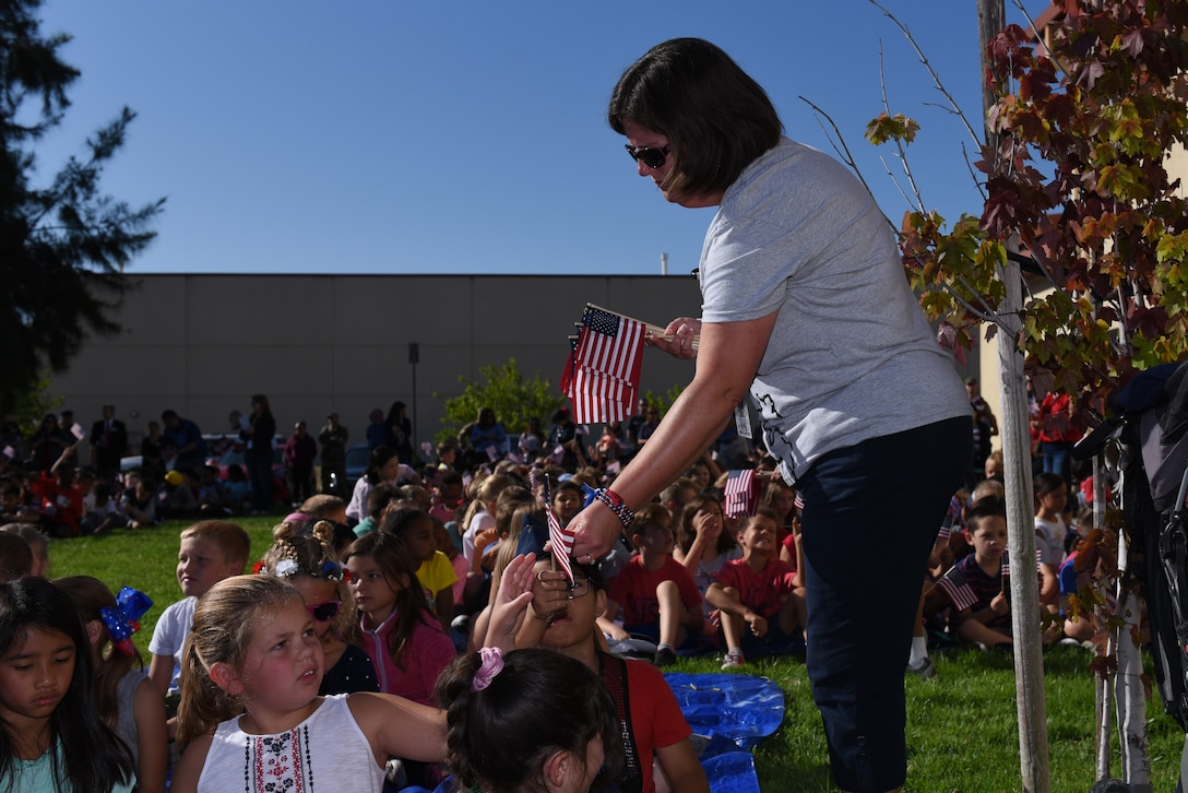 American Flags are handed out to children attending the Remembrance Day Freedom Walk Sept. 11, 2019, at Travis Air Force Base, California. The walk commemorated those who lost their lives on 9/11. (U.S. Air Force photo by Airman 1st Class Cameron Otte)
