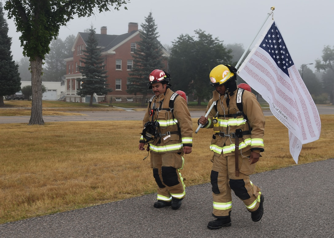 Senior Airman Ralph Mesidor and Cody Woolett, members of the Warren Fire Department, carry the Flag of Heroes around the base parade field Sept. 11 on F. E. Warren Air Force Base. Firefighters conducted the 24 hour vigil in firefighter gear honoring those who were killed in the attacks of Sept. 11, 2001.