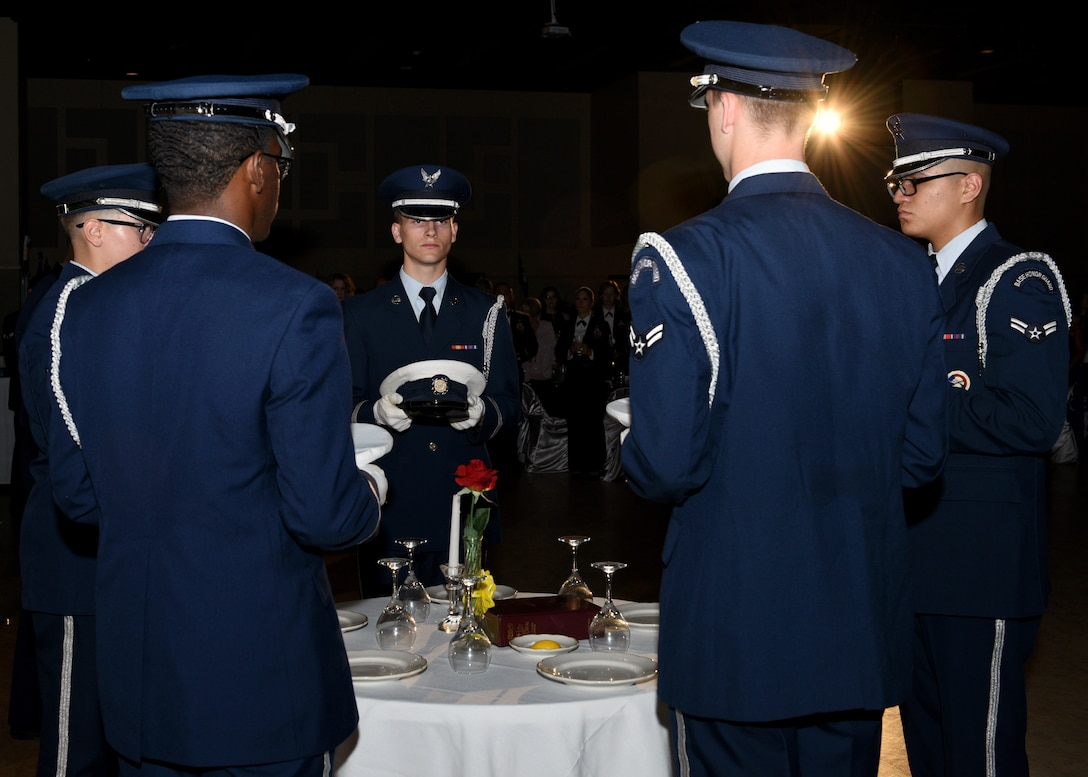 Goodfellow Honor Guard members place covers on the POW/MIA table during the 2019 Air Force Ball at the McNease Convention Center in San Angelo, Texas, September 7, 2019. The POW/MIA table has been a military tradition since the end of the Vietnam War, a place setting for one, a table for all. (U.S. Air Force photo by Airman 1st Class Robyn Hunsinger/Released)