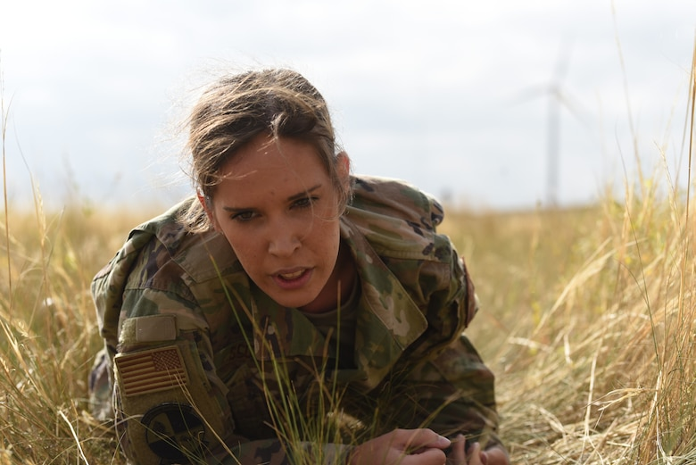 Airman 1st Class Hannah Scott, defender with the 890th Security Forces Squadron, low crawls through the dirt and tall grass during the annual Crow Creek Challenge Sept. 6, 2019, at F. E. Warren Air Force Base, Wyo. When she reached the end of the line, she rose and fireman carried her teammate back across the field to complete the obstacle. The Crow Creek Challenge included many other physical activities that teams were expected to complete throughout the long day. (U.S. Air Force photo by Senior Airman Nicole Reed)