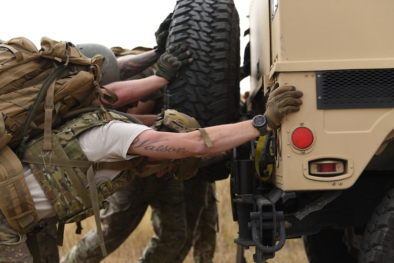 Security forces members from Team Guernsey show their strength during the HMMWV push at the annual Crow Creek Challenge Sept. 6, 2019, at F. E. Warren Air Force Base, Wyo.  They pushed the heavy vehicle down the intended path before reaching a small dip in the ground they had to overcome. After a brief moment of difficulty, they gave one final heave and got the vehicle over the small ditch to complete the task. (U.S. Air Force photo by Senior Airman Nicole Reed)