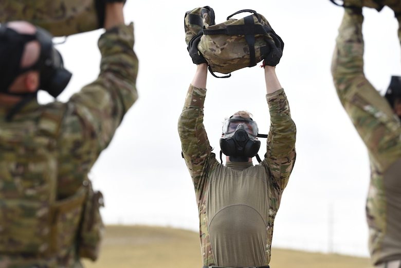 Airmen don their gas masks and complete a set of workouts to include overhead sandbag presses during the Crow Creek Challenge Sept. 6, 2019, at F. E. Warren Air Force Base, Wyo. The heavy bags were also used in other activities like a high-crawl bag toss and numerous calisthenic workouts. This obstacle was just one of many physical obstacles security forces members took part in during the challenge. (U.S. Air Force photo by Senior Airman Nicole Reed)