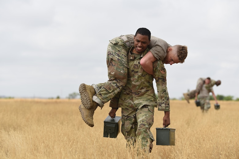 Airman 1st Class Leomar Perez, defender with the 890th Security Forces Squadron, fireman carries Airman 1st Class Jacob Boyett from the 890th Security Forces Squadron, along with two ammo cans during the Crow Creek Challenge Sept. 6, 2019, at F. E. Warren Air Force Base, Wyo. The obstacles seen throughout the day included heavy lifting, running, and calisthenic exercises. (U.S. Air Force photo by Senior Airman Nicole Reed)