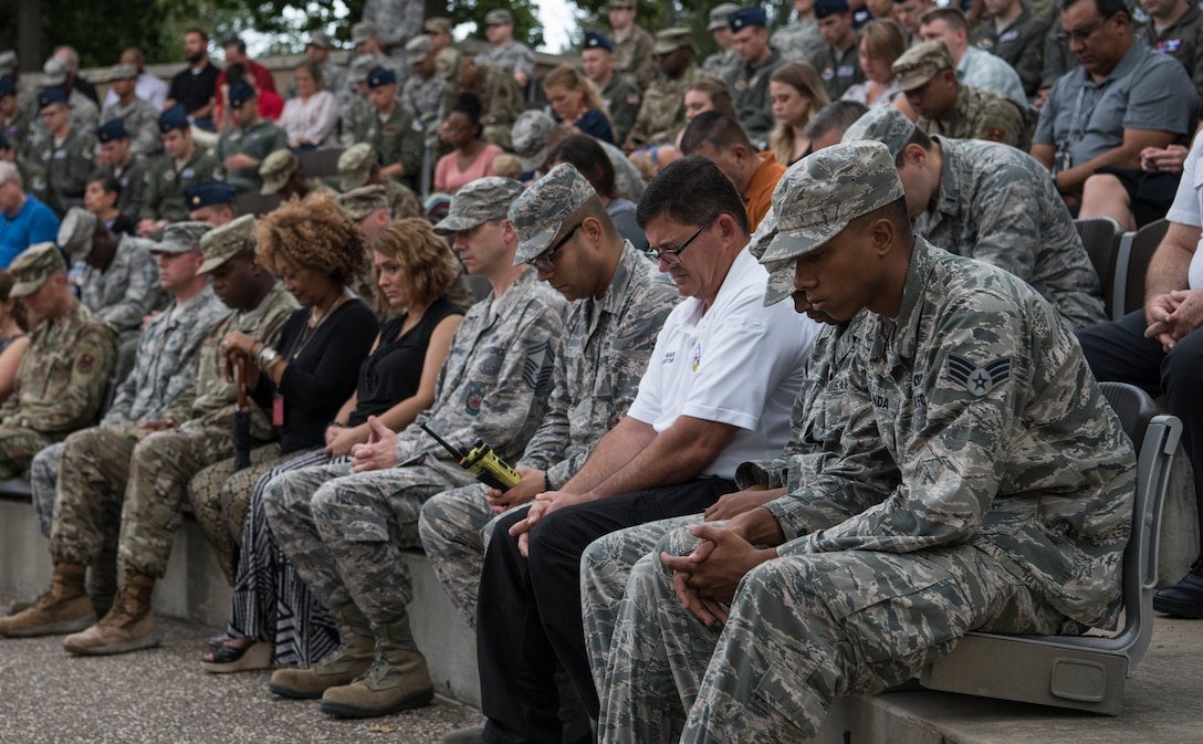 Airmen assigned to the 47th Flying Training Wing join in prayer during a 9/11 memorial ceremony at Laughlin Air Force Base, Texas, Sept. 11, 2019. Approximately 230 Laughlin Airmen gathered at the flag pole in remembrance of the nearly 3,000 people killed in the attacks. (U.S. Air Force photo by Staff Sgt. Benjamin N. Valmoja)