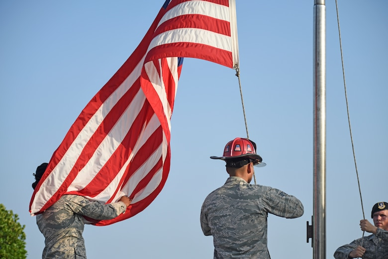Members of the 8th Security Forces Squadron and 8th Civil Engineer Squadron lower the flag during the national anthem at the September 11 Remembrance ceremony at Kunsan Air Base, Republic of Korea, Sept. 11, 2019. The ceremony was held in remembrance of the 2,977 people who lost their lives on Sept. 11, 2001, in New York City, Washington, D.C., and outside Shanksville, Pennsylvania. The ceremony included a ringing of a bell, F-16 Fighting Falcon flyover and flag folding and presentation. (U.S. Air Force photo by Staff Sgt. Mackenzie Mendez)