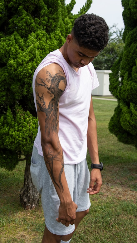 U.S. Air Force Airman 1st Class D'Andre Daniels, a 35th Aircraft Maintenance Squadron crew chief, reveals his tattoos at Misawa Air Base, Japan, Aug. 8, 2019. For this one individual in particular, his tattoos are a reminder of where he used to be, where he never wants to be again and where he needs to go. (U.S. Air Force photo by Airman 1st China M. Shock)