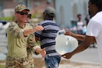 A U.S. Coast Guardsman provides water to those affected by Hurricane Dorian in the Bahamas, Sept. 8, 2019.  DLA Troop Support provided more than 1,400 cases of bottled water to various Department of Defense customers in support of the hurricane relief efforts. (U.S. Coast Guard Courtesy Photo)