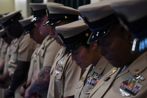 Sailors bow their heads for the invocation during a chief petty officer pinning ceremony held on board Naval Support Activity Bahrain. 39 Sailors from U.S. Naval Forces Central Command, Naval Support Activity Bahrain, and commands located throughout the U.S. 5th Fleet area of operations received their anchors.