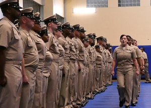 Chief petty officer selectees sing Anchors Aweigh as they make their entrance into a chief petty officer pinning ceremony held on board Naval Support Activity Bahrain. 39 Sailors from U.S. Naval Forces Central Command, Naval Support Activity Bahrain, and commands located throughout the U.S. 5th Fleet area of operations received their anchors.