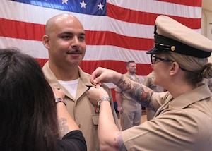 hief Cryptoplogic Technician (Technical) Eric Dejesus has anchors pinned on by his wife, left, and Senior Chief Cryptologic Technician (Collection) Hannah Ryder during a chief petty officer pinning ceremony held on board Naval Support Activity Bahrain. 39 Sailors from U.S. Naval Forces Central Command, Naval Support Activity Bahrain, and commands located throughout the U.S. 5th Fleet area of operations received their anchors.