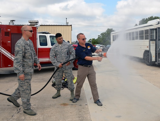 Steve Young, VIA Metropolitan Transit vice president of information technology, experiences discharging a fire hose during a tour of the 433rd Mission Support Group at Joint Base San Antonio-Lackland Sept. 7. Young is paired with Lt. Col. Travis J. Hatley, 74th Aerial Port Squadron commander.
