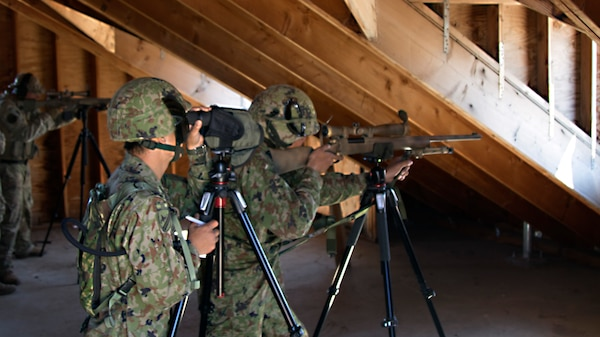 A sniper team from the 25th Infantry Regiment aims to fire while the sniper team from the 2-130th Infantry Regiment fires alongside them during Rising Thunder 2019.