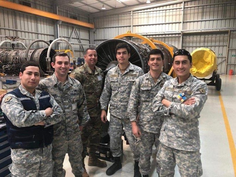 U.S. Air Force Airmen and Chilean airmen stop training to pose for a photo August 26, 2019 at Cerro Moreno Air Base, Chile. The U.S. Airmen were on a temporary duty where they ceritified 15 Chilean airmen on how to perform repairs on F100-Pratt and Whitney-W220 jet engine fan blades. (Courtsey photo)