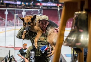 Tech. Sgt. Tyler Hendrix, 56th Security Forces Squadron kennel master, carries a military working dog during the 9/11 Tower Challenge Sept. 11, 2019, at the Gila River Arena, Glendale, Ariz.