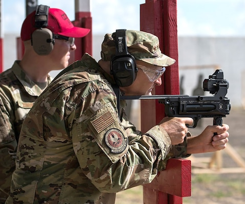 Gen. Arnold W. Bunch, Jr., fires the M320A1 grenade launcher with the ballistic sighting module aiming device with guidance from Staff Sgt. Brett Miner, 37th Training Support Squadron combat arms instructor, at Medina range during his visit to Air Force Materiel Command Units at Joint Base San Antonio Sept. 4.