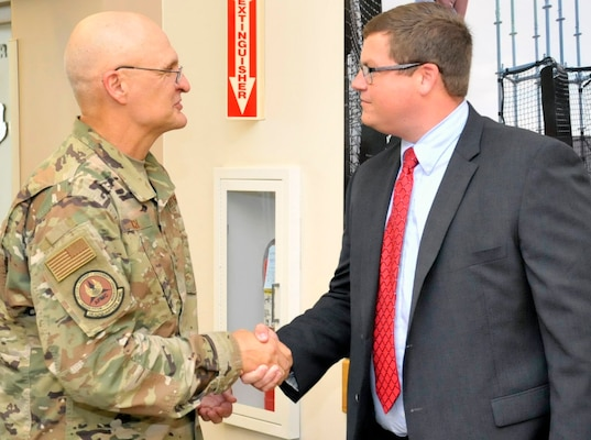 Gen. Arnold W. Bunch, Jr., Air Force Materiel Command commander, gives one of his commander's coins for excellence to Waid Harper of the 338th Specialized Contracting Squadron at Air Force Installation and Mission Support Center headquarters at Joint Base San Antonio-Lackland Sept. 4.