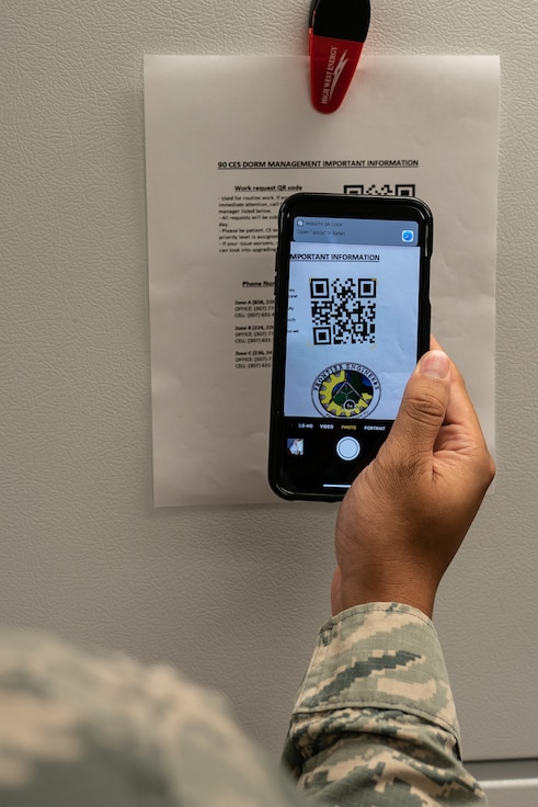 Senior Airman Wil Yau, 90th Communications Squadron client systems technician and originally from Kissimmee, Fla., demonstrates the quick response code dormitory work order process Sept. 10, 2019, at F.E. Warren Air Force Base, Wyo. Yau and the dormitory management team created an improved dorm maintenance work order process to make it more convenient for Airmen to report issues. (U.S. Air Force photo by Joseph Coslett)