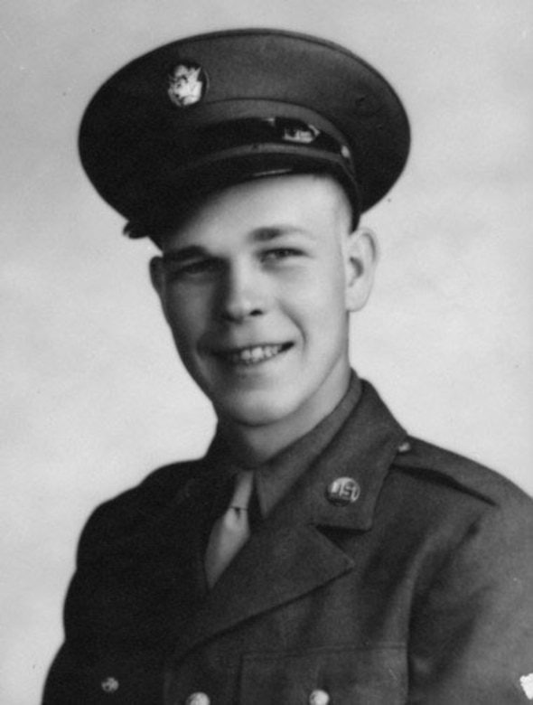 A young man smiles in his Army dress uniform jacket and cap.