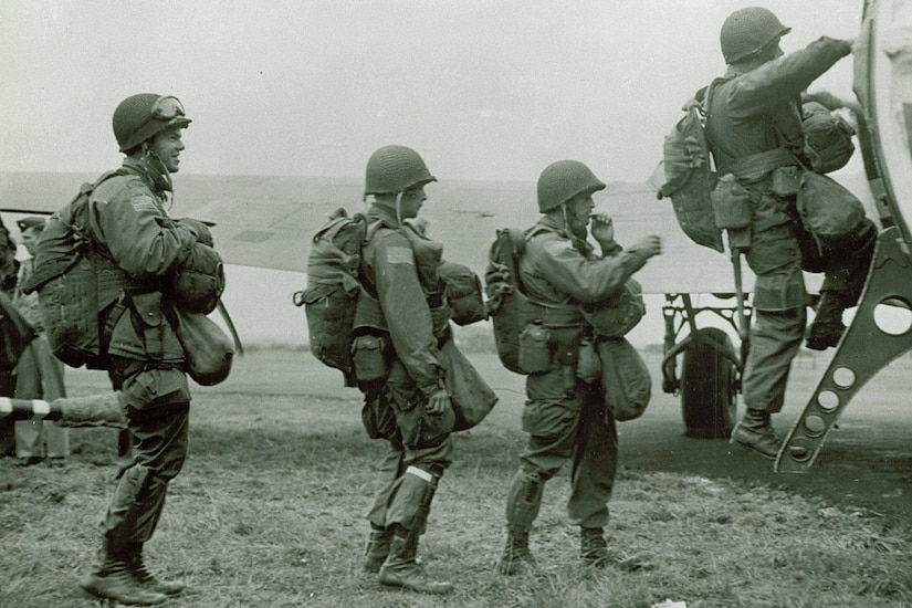 Three Army paratroopers in battle uniform and wearing parachutes and helmets stand in line to climb into an airplane as a fourth soldier heads inside.