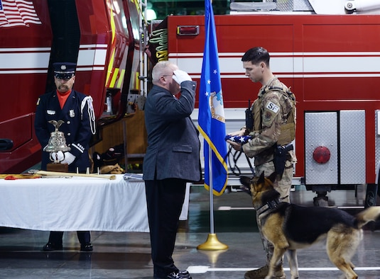Ron Roen salutes the American flag that a military working dog handler is holding.