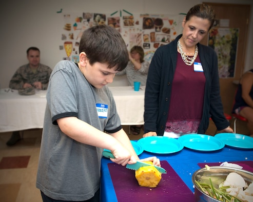 Alicia Newton (right), Nutritionist and Founder of Nourish My Soul and the associated Jr. Chef Boot Camp, looks on as Jr. Chef Haakon (left), slices a pineapple, July 26, 2019 at Holcomb Farm in Granby, Conn. Founded in 2018, the Jr. Chef Boot Camp provides cooking lessons for the children of service members in Connecticut. The boot camp was the first culinary arts program to be awarded a grant by the Hartford Arts Council when it began in 2018. The goal of the boot camp is to teach children healthy cooking and eating habits before they reach adulthood. The boot camp concludes with a cooking competition.