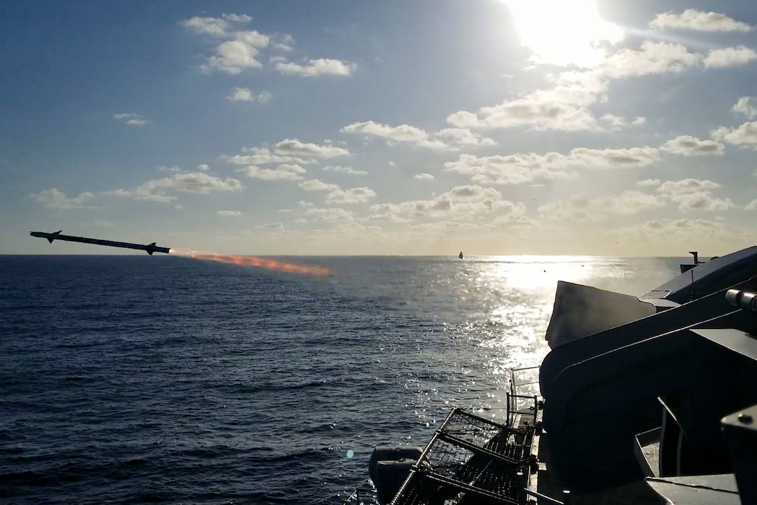 A missile flies through the air over the ocean after being launched from a military ship.