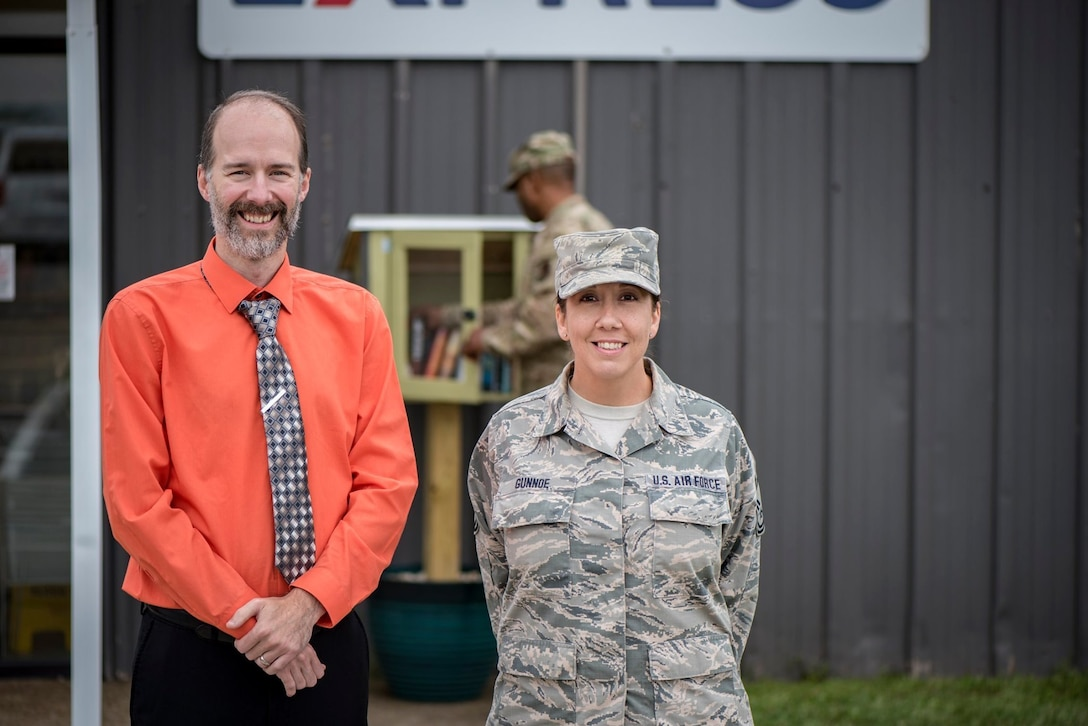 Environmental portrait photo of a military member posed with a civilian in front of a Little Free Library.