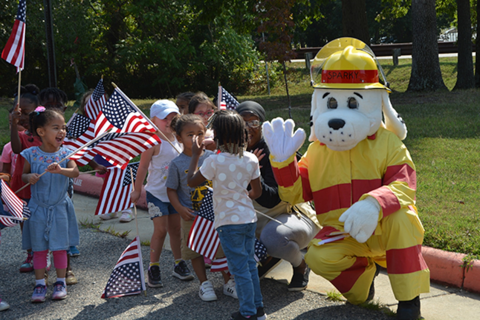 Children walk with Sparky, the fire dog