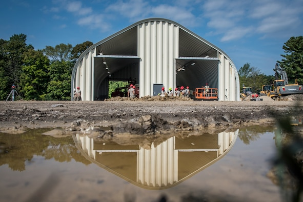 Wide landscape photo of a building and military members with its reflection in a puddle of water.