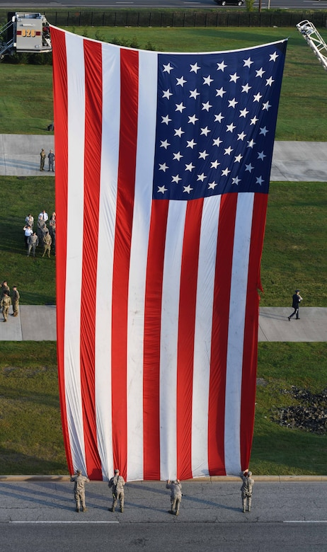 Joint Base Andrews Airmen hold a flag taut during the 9/11 memorial ceremony on Joint Base Andrews, Md., Sept. 11, 2019.  Nearly 3,000 people lost their lives after the terrorist attacks on Sept. 11, 2001. (U.S. Air Force Photo by Airman 1st Class Spencer Slocum)