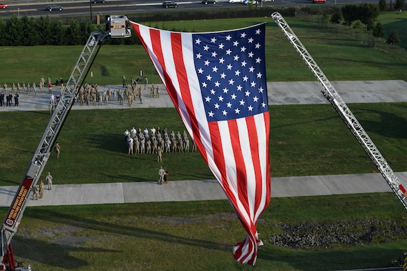 An American flag waves in the wind during the 9/11 memorial ceremony on Joint Base Andrews, Md., Sept. 11, 2019. The flag was draped between two fire truck ladders to honor the first responders who lost their lives after the 9/11 attacks in 2001. (U.S. Air Force photo by A1C Spencer J. Slocum)