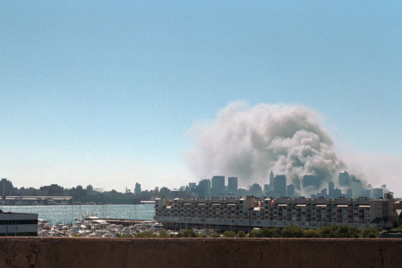 Smoke rises from the World Trade Center. The New York City skyline is also visible in the background. A large ship and some smaller boats are seen in the foreground.