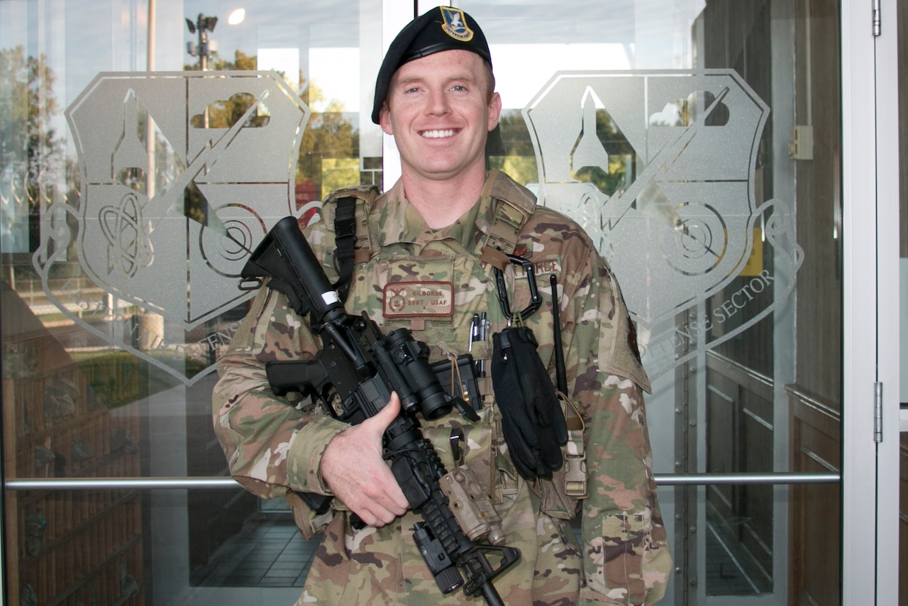 A smiling security forces airman dressed in fatigues points his weapon toward the ground as he stands in front of glass doors etched with the Air Defense Sector insignia.
