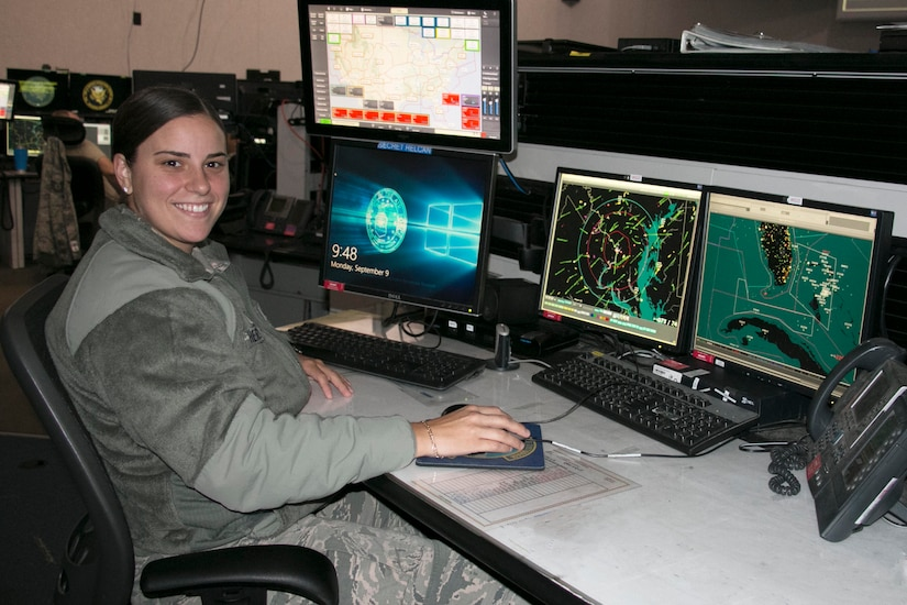 A smiling female airman sits at a desk with four computer monitors. Two of the monitors display maps.