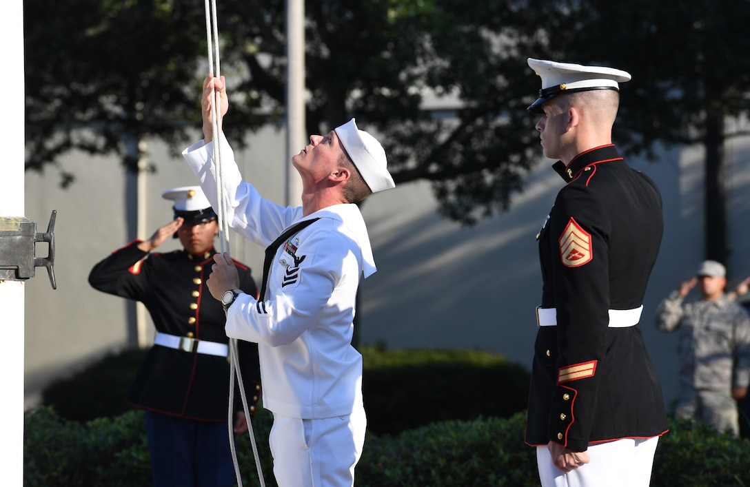 U.S. Navy Aerographers Mate 1st Class Daniel Ealy, Center for Naval Aviation Technical Training Unit Keesler instructor, raises the U.S. flag as U.S. Marine Staff Sgt. Jacob Nixon, Keesler Marine Detachment curriculum manager, renders a salute during a 9/11 memorial ceremony hosted by CNATTU Keesler in front of the 81st Training Wing headquarters building on Keesler Air Force Base, Mississippi, Sept. 11, 2019. The event honored those who lost their lives during the 9/11 attacks. (U.S. Air Force photo by Kemberly Groue)