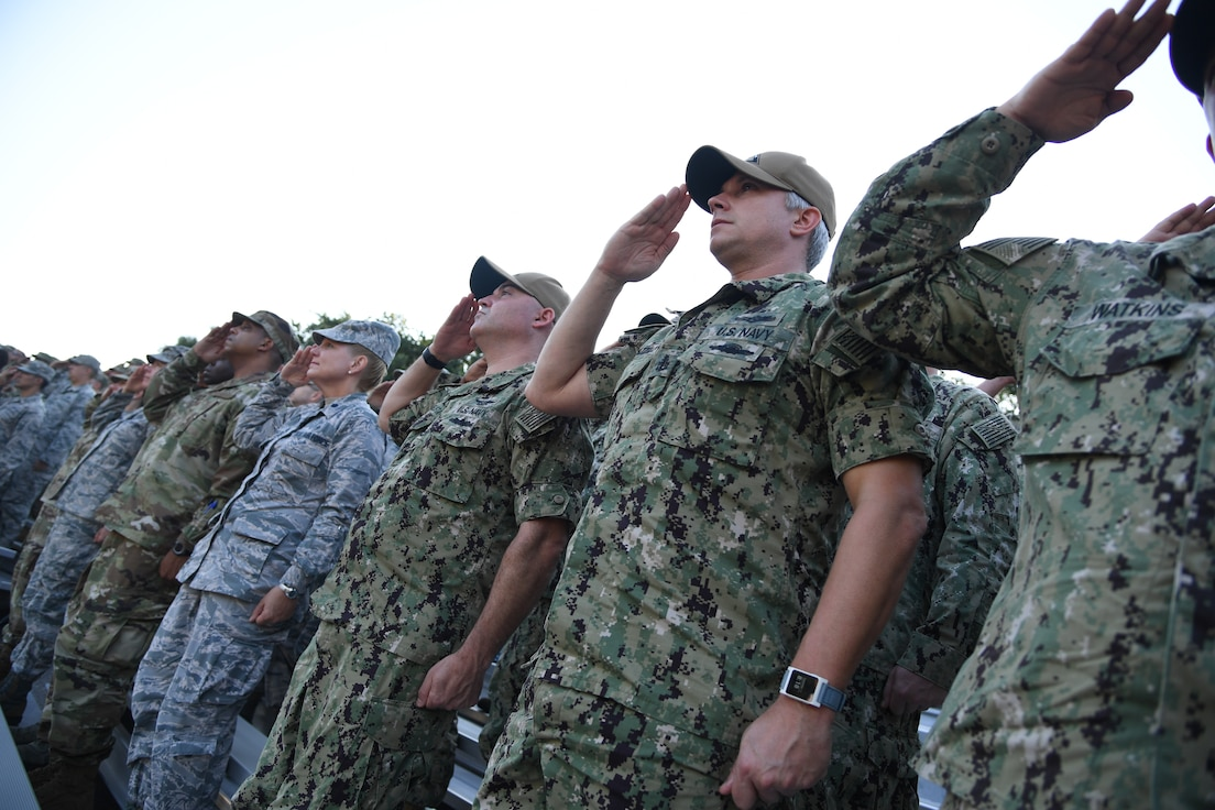 Keesler Airmen, Sailors and Marines render a salute during a 9/11 memorial ceremony hosted by the Center for Naval Aviation Technical Training Unit Keesler in front of the 81st Training Wing headquarters building on Keesler Air Force Base, Mississippi, Sept. 11, 2019. The event honored those who lost their lives during the 9/11 attacks. (U.S. Air Force photo by Kemberly Groue)