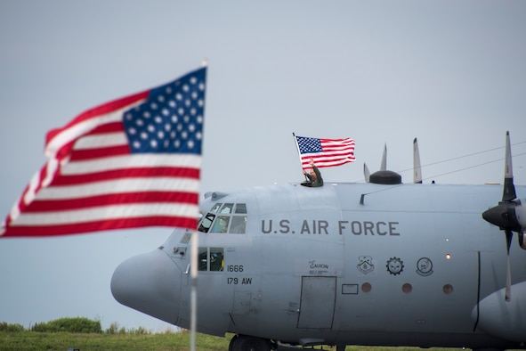 Photo of a C-130 passing behind the U.S. American flag