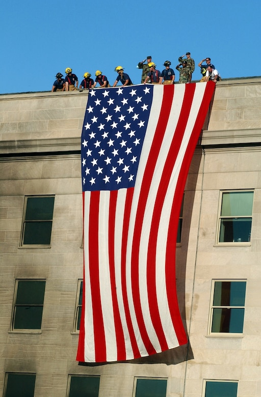 Military members, firefighters and rescue workers unfurl a huge American flag over part of the Pentagon, covering windows on two floors.