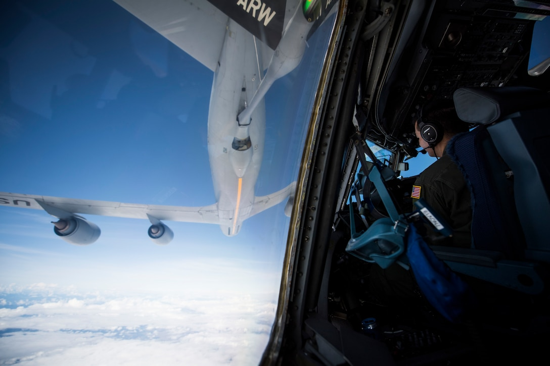 An Air Force pilot watches as his plane approaches another military aircraft.