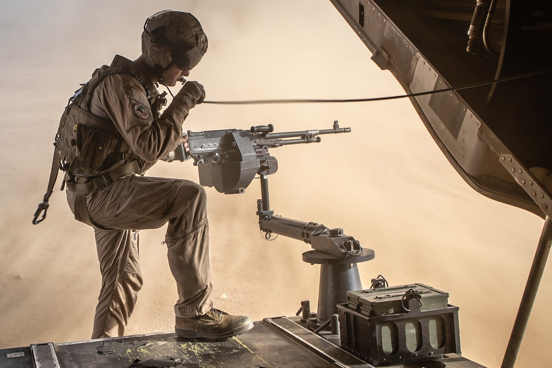 A Marine stands half inside an open aircraft and half on sand below and points an attached machine gun