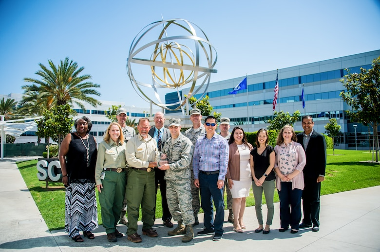 Mr. Bob Baird (third left), the Director, and Ms. Nicole Williams (second left), the Deputy Director, of Fire and Aviation Management from the Pacific Southwest Region of the U.S. Forest Service visited the Space and Missile Systems Center July 26, 2019. They came to recognize the hard work by men and women of the SMC for their support to the US Forest Service in providing timely data during the 2018 fire season.