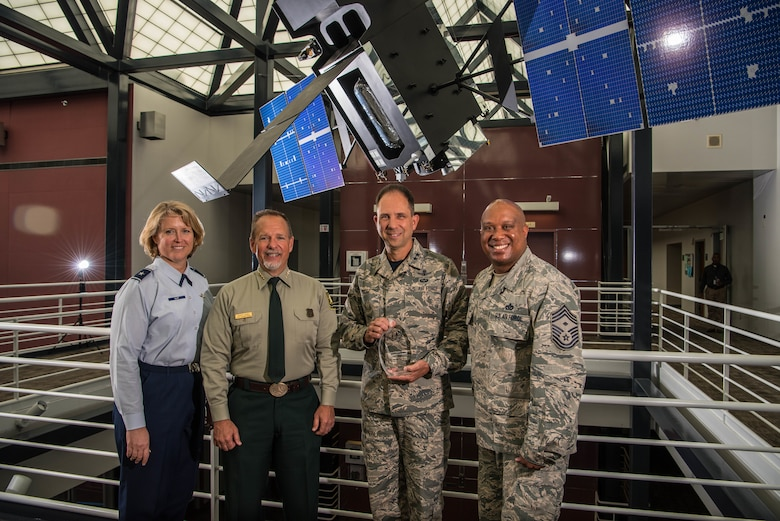 The U.S. Forest Service presented an award to Air Force Space Command April 26, 2019, at Peterson Air Force Base, Colo. in recognition of the command's contributions to fighting wildfires in California in November 2018 by providing fused remote sensing data to the USFS regional firefighting operations center. From left to right are: Brig. Gen. Deanna Burt, AFSPC Director of Operations and Communications; Robert Baird, regional director of the Fire and Aviation Management, Pacific Southwest Region, U.S. Forest Service; Maj. Gen. John Shaw, AFSPC deputy commander; and CMSgt Daryl Hogan, former AFSPC First Sergeant and career Air Force firefighter.