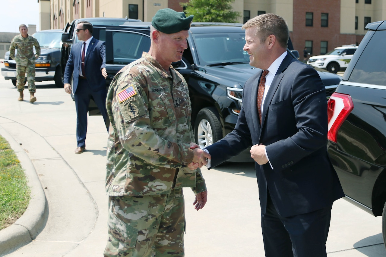 Two men shake hands. One is wearing a military uniform and a green beret; the other is wearing a dark suit.